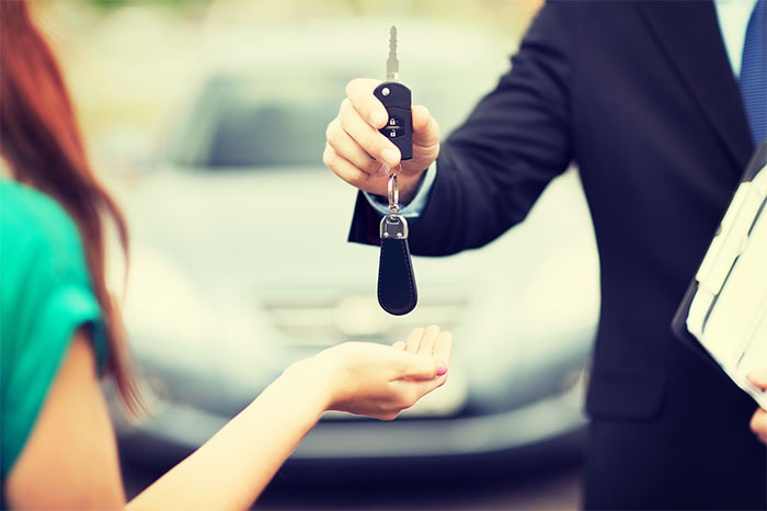 car-salesman-handing-keys-to-female-driver-main-2
